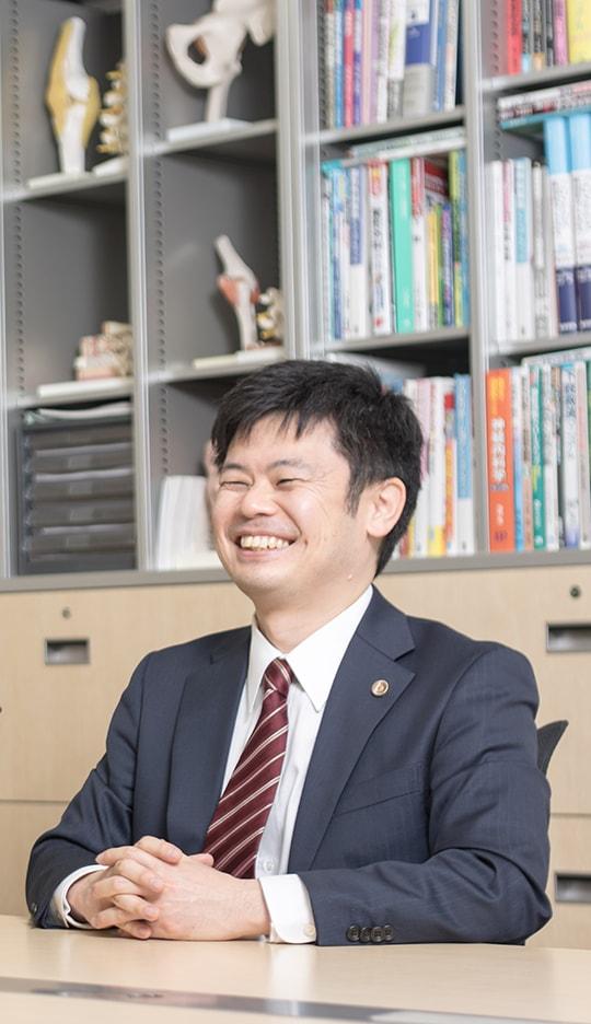 笑顔で座っている弁護士深田先生の写真