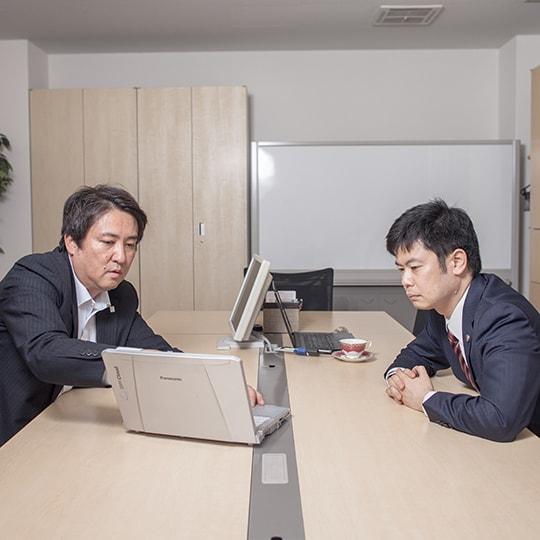 真面目な顔でパソコンをのぞき込む深田先生と弊社代表の写真