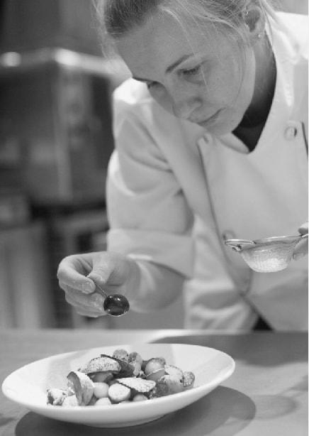白人女性のシェフが料理をしている写真(モノクロ)
